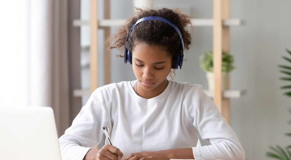 Focused teen girl wearing headphones and writing notes while studying