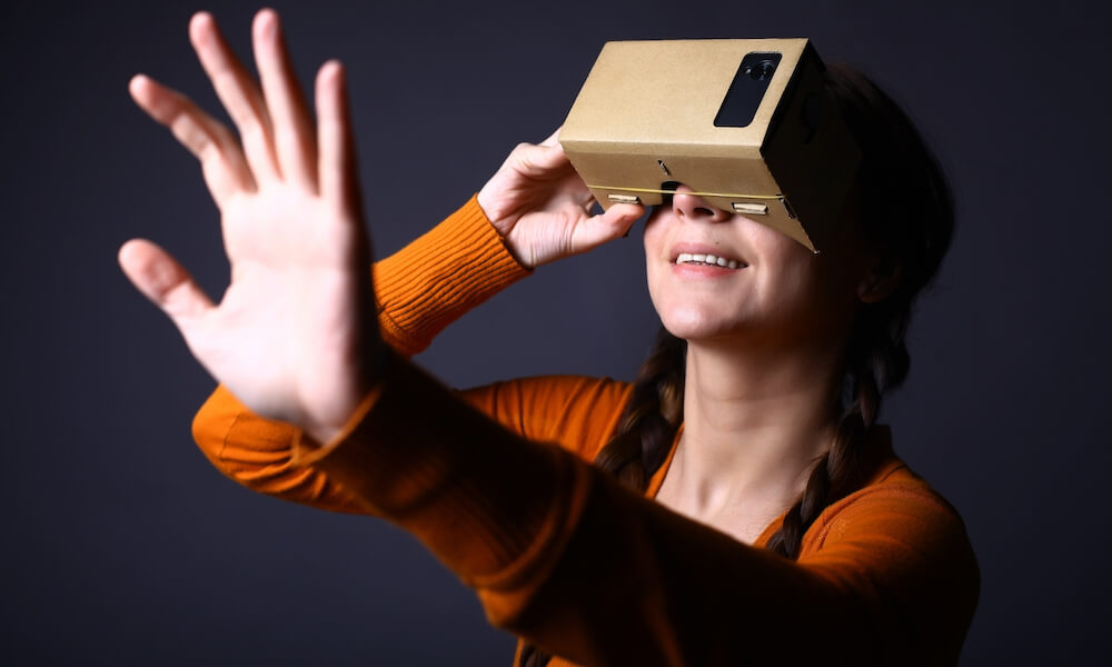 Girl looking through a cardboard device with which one can experience virtual reality on a mobile phone