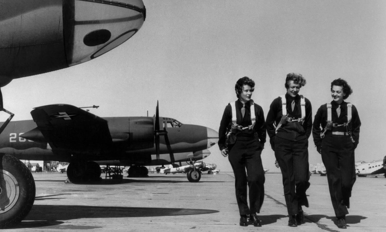 three female pilots walking by military planes