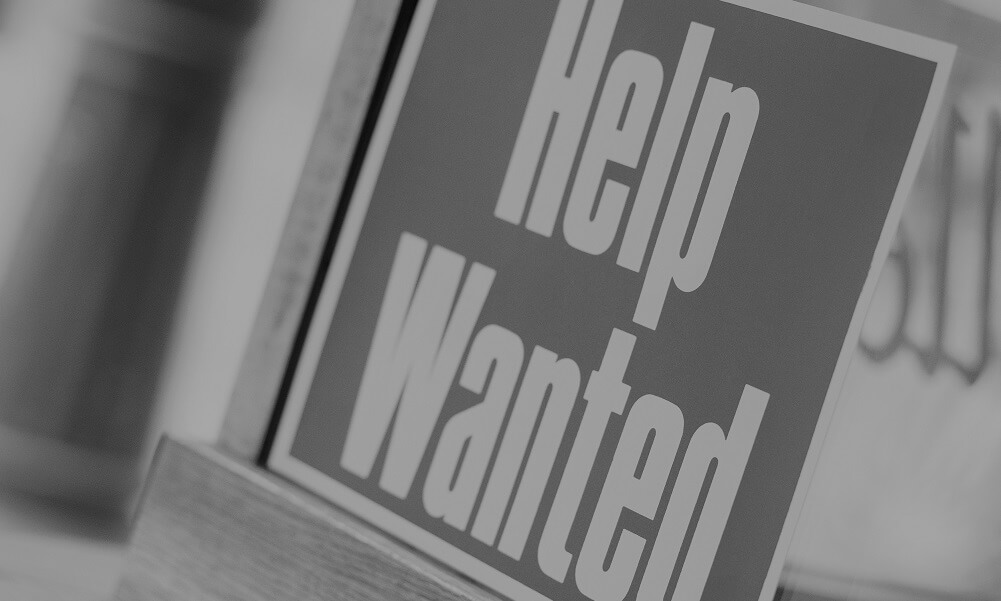 """A """"Help Wanted"""" sign in a shop window"""