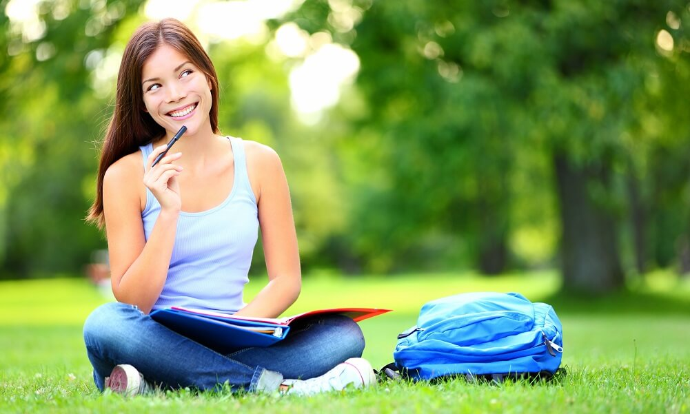Student studying while sitting on the grass at a university campus park