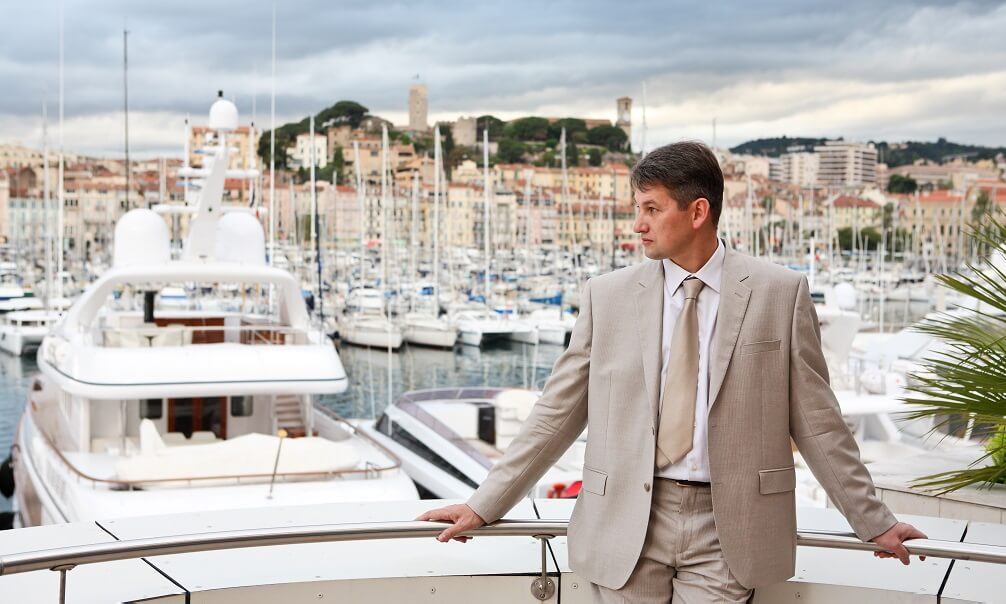 White man on the balcony of Palais des Festivals in Cannes, France, yachts in marina in background