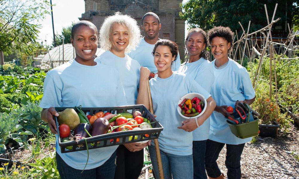Volunteers holding vegetables in community garden
