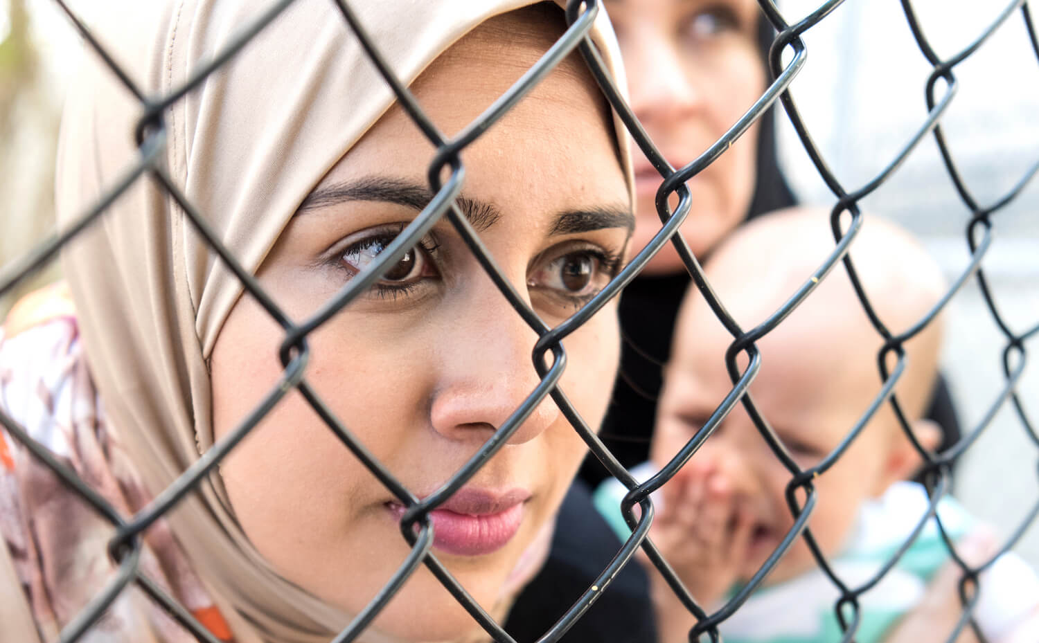 Somber Middle eastern women looking through a fence; one is holding a crying baby
