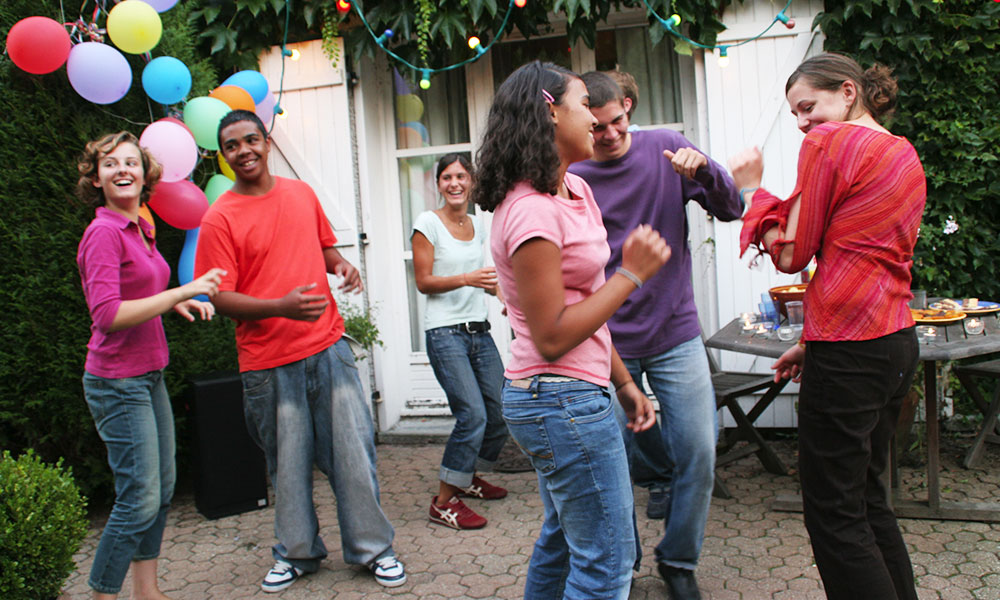 Teens dancing on a patio in Paris, France