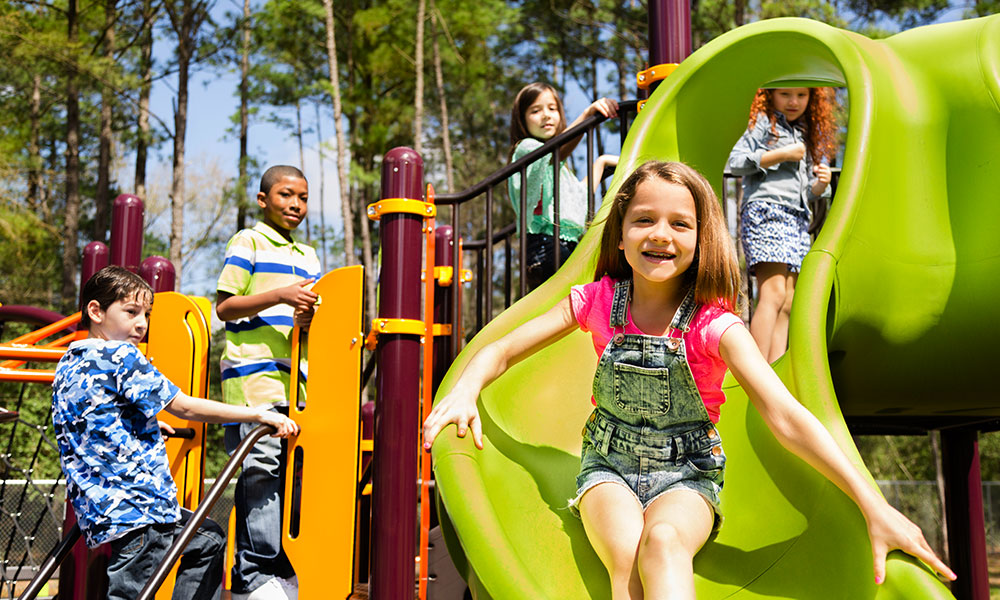 Five elementary-age children play during school recess or at a park setting. Playground equipment, slide.