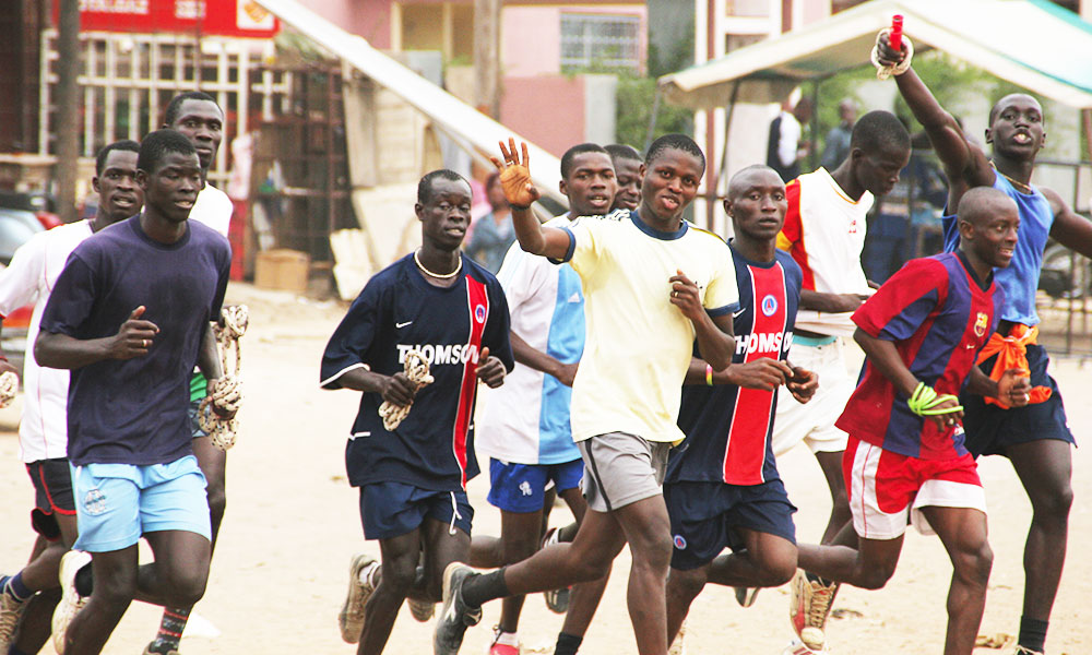A group of small African boys running through the streets