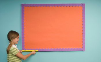 Student holding a 1-foot ruler left aligned with the left edge of a small bulletin board