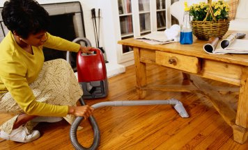 Woman vacuuming under a table