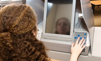 Eighteen year old girl voting for the first time on a touch screen machine