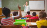 Teacher calling on pupil with raised hand during class