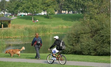 A girl and her dog and a bicycle rider at the Cartier-Brebeuf park in Quebec City, Canada