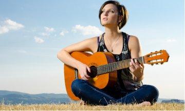 Female guitarist sitting outside in a field