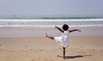 Rear view of an african american girl standing on one leg on the beach