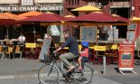 A man and child ride a bicycle in front of cafes on the the Rue Champ Jacquet in Rennes, France.