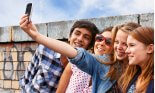 Teenage friends photographing themselves with smartphone
