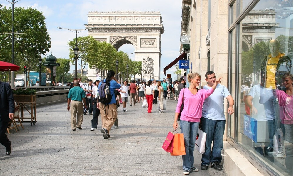 One teen boy and one teen girl shopping along the Avenue des Champs Elysees, stores, shops, commerce, Paris, France, Europe, Arc De Triomphe in the background.