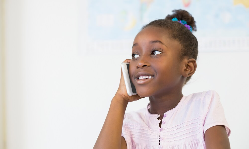 Smiling schoolgirl talking on mobile phone in classroom at school