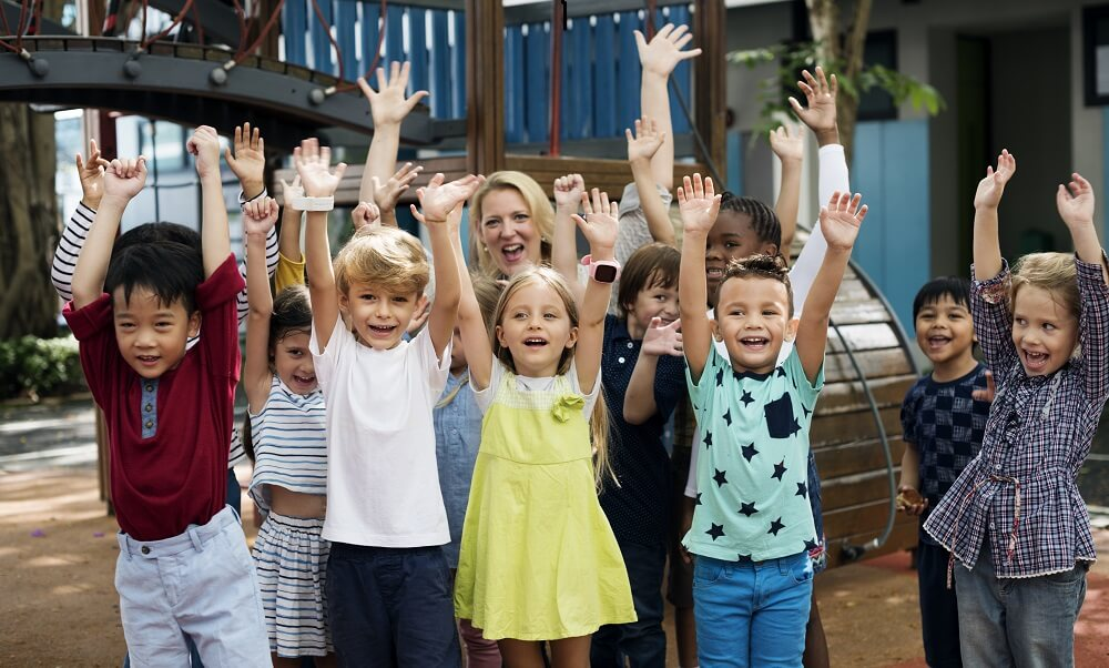 Kindergarten students with arms raised