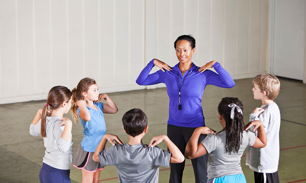 African American woman (30s) teaching a physical education class with elementary age children (7-9 years).
