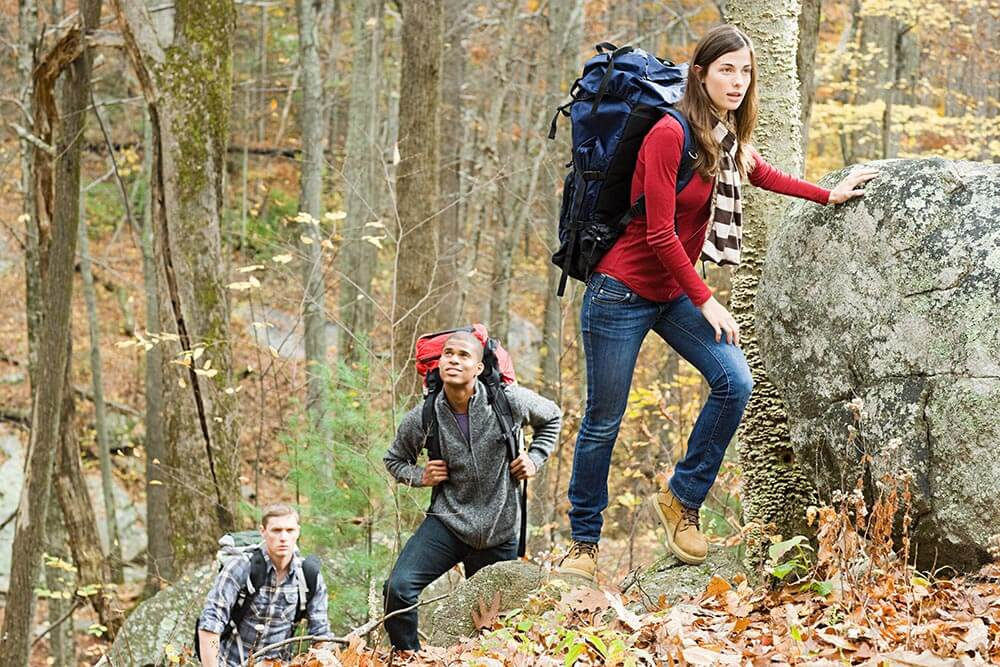Young people with backpacks hiking in the woods