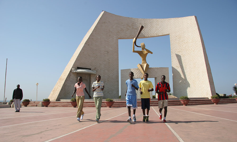 Youth jogging in front of Dakar sculpture