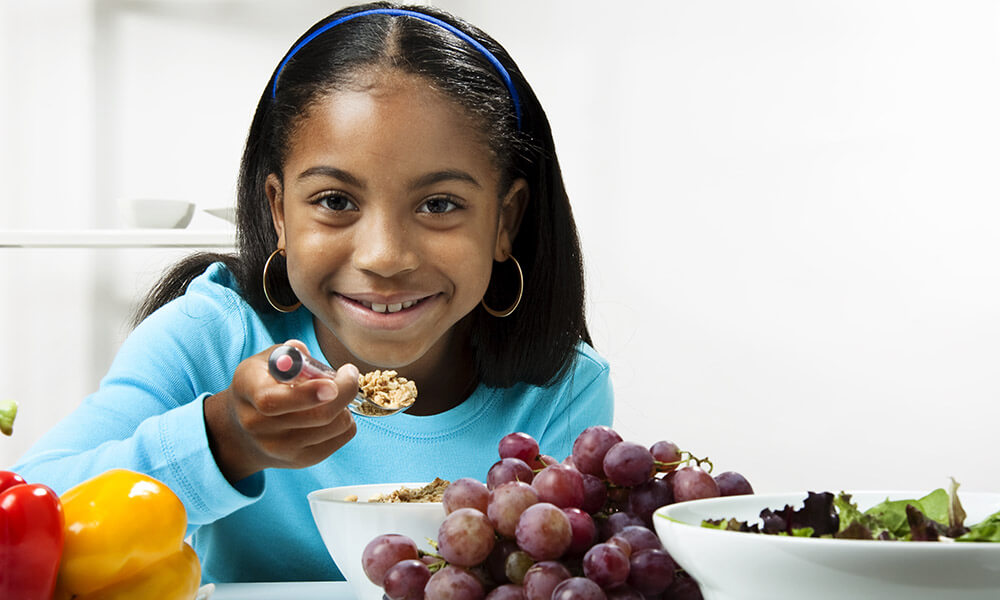 Young black girl (10-11 years old) eating a healthy salad