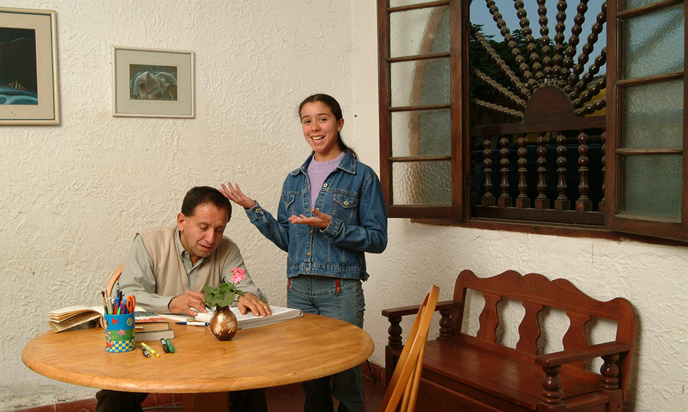 Teen and father doing homework at dining room table