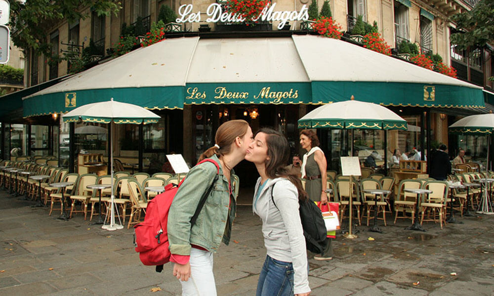 Two young women kiss in front of Les Deux Magots cafe