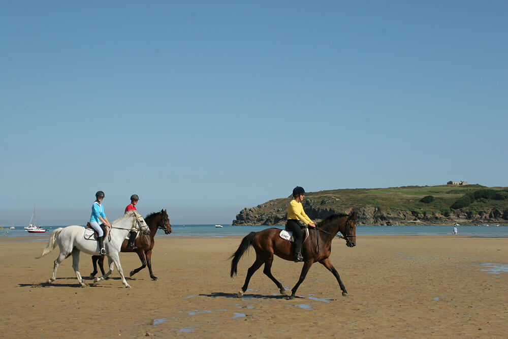 Three horseback riders at the Plage du Lupin, Rotheneuf, Saint Coulomb, Saint Malo, Brittany, France