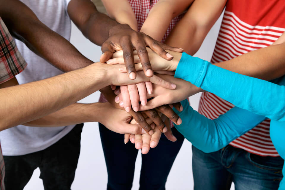 A group of children with their hands together