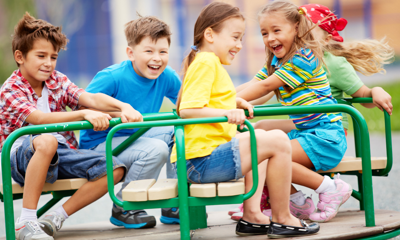 Happy kids playing on a merry-go-round in a playground.