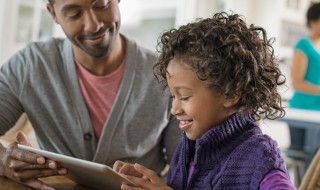 A girl and her father looking at a digital tablet.