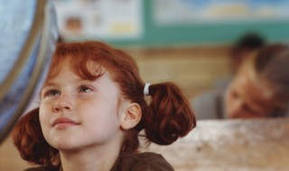 A girl in pigtails stares at a world globe.