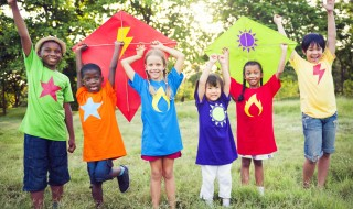 A group of kids in a grassy field, holding two colorful kites over their heads.