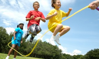 A smiling boy and girl jumping over a skipping rope.