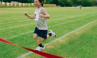 A smiling boy running towards the red tape of a finish line on a grass running track.