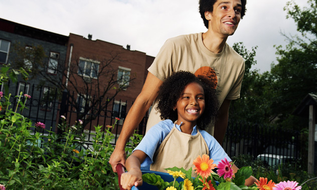 A smiling father and daughter pushing a wheelbarrow full of flowers in a city garden.