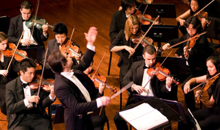 A conductor conducting an orchestra of musicians.