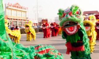 A group of lion dancers marching in a street, dressed in colorful Kei Lun dance costumes.