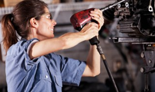 A smiling woman using a power drill to fix a car in an auto repair shop.