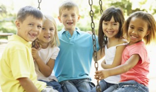 Five smiling kids sitting together on a swing in a playground.