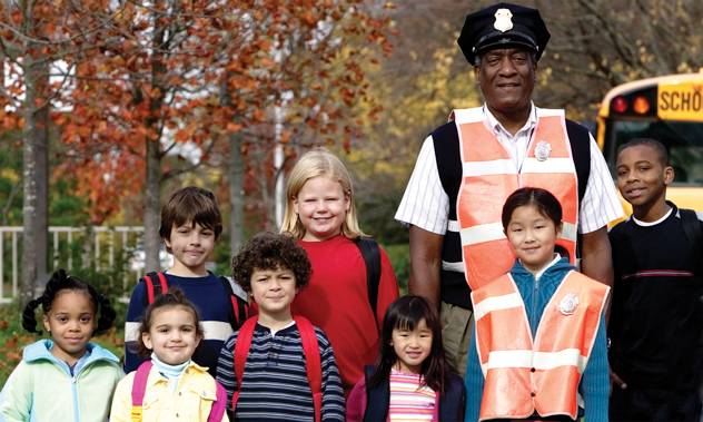A friendly school-bus driver standing with a group of smiling kids on their way to school.