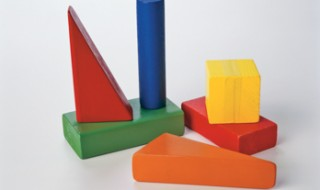 Colorful wooden triangles and rectangle, with a cube and a cylinder.