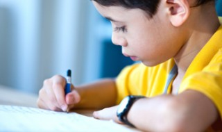 A boy writing with a pen.