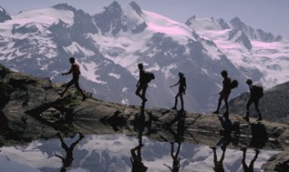 A group of people walking by a small lake with tall mountains covered in snow behind them.