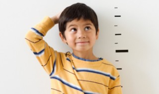 A boy looking at how tall he is using marks on a wall.