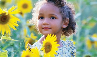 A girl standing in a field of yellow sunflowers.