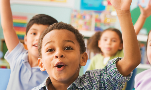 A group of happy kids in a classroom raising their hands to answer a question.
