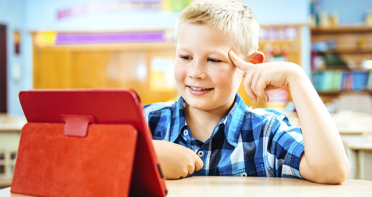 A boy looks at a digital tablet in a classroom.
